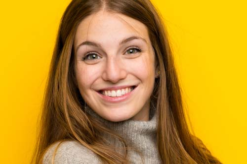 cosmetic dentistry woman smiling yellow background
