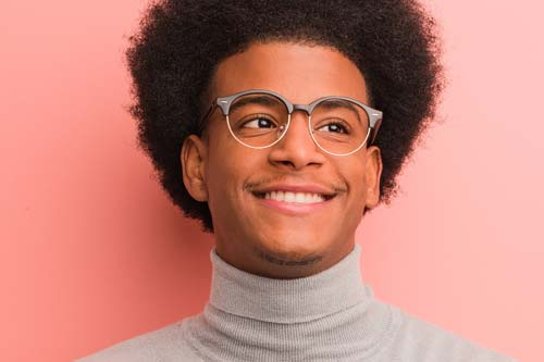 specialist services man in glasses smiling pink background