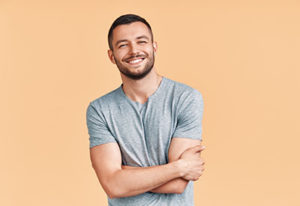 man smiling on orange background for general dentistry Sugar Land tx after houston tx general dentistry services