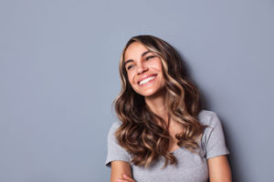 woman smiling on gray background for teeth cleaning Sugar Land texas services including teeth cleaning and dental exams