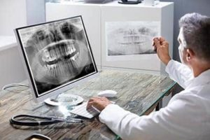 dentist performing an oral cancer screening