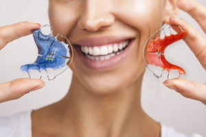 Woman shows her retainers as a part of her orthodontics care